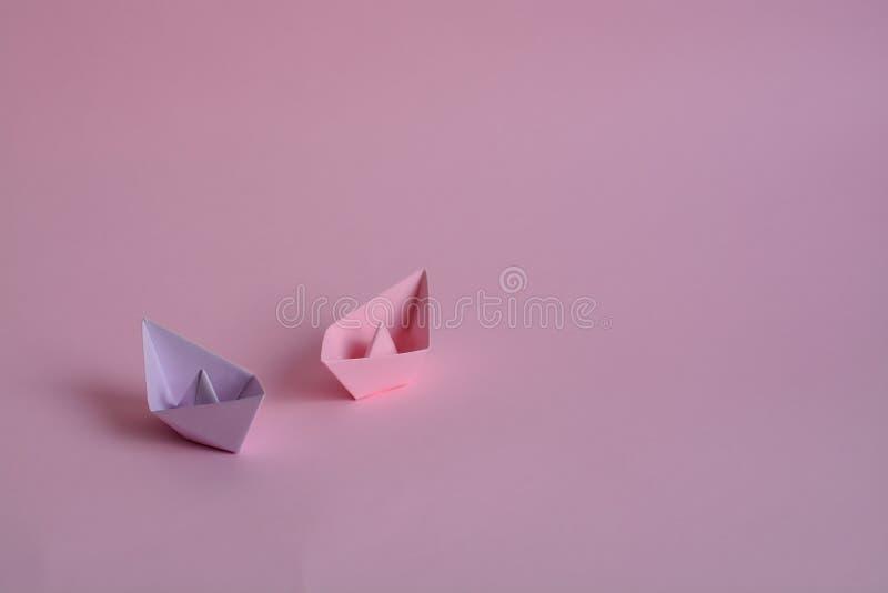 Lilor och rosa pappers- fartyg på pastellfärgade rosa färger arkivfoto