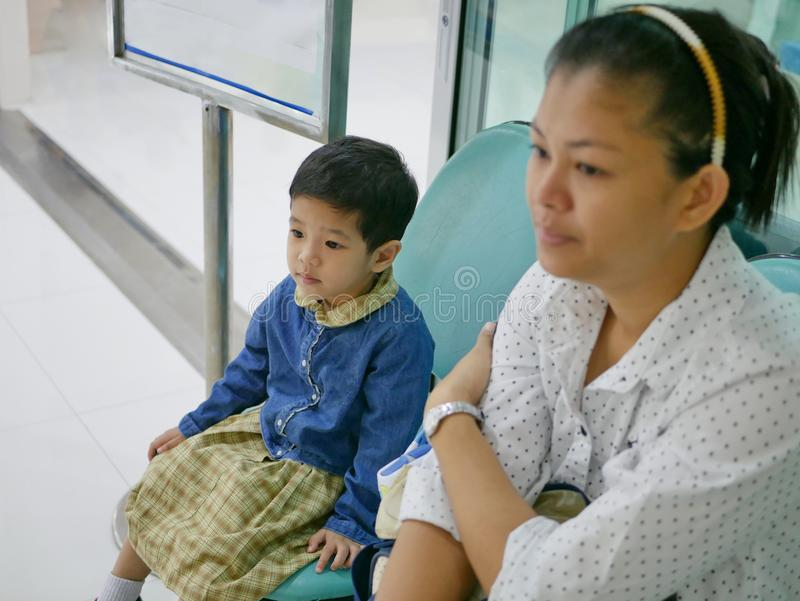 Lilttle Asian baby, together with her mother, sitting in a hospital waiting for her queue to see a doctor stock photography