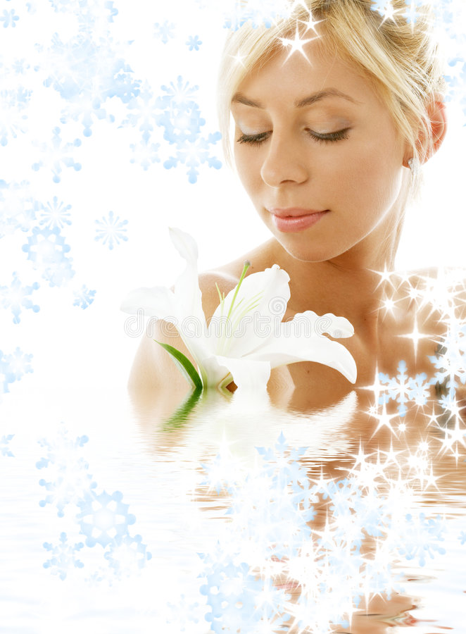 Lily blond in water with snowflakes. Pretty lady with madonna lily in water with snowflakes royalty free stock photos