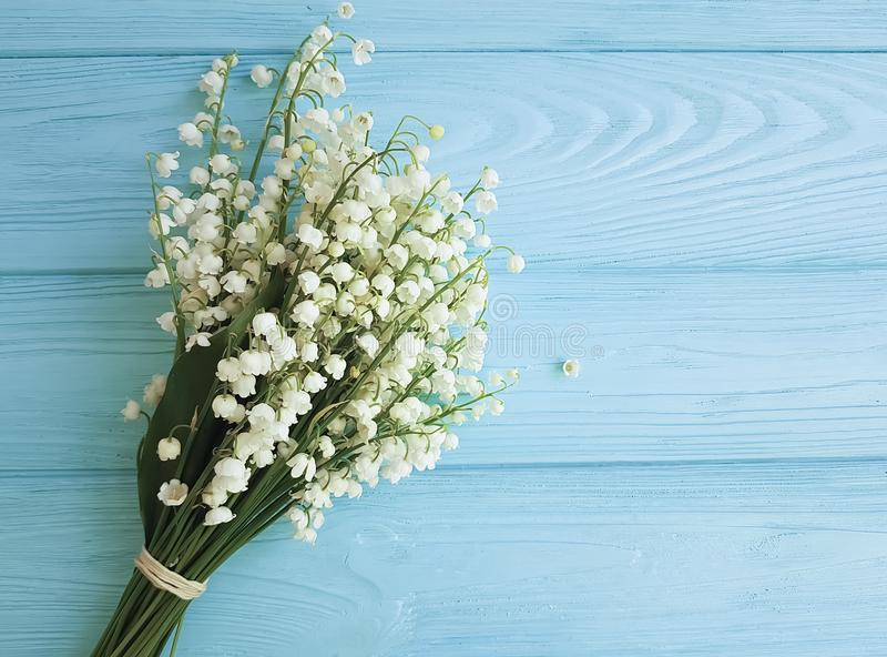 Lily of the valley element greeting on a blue wooden background. Lily of the valley a blue wooden background element greeting stock photo