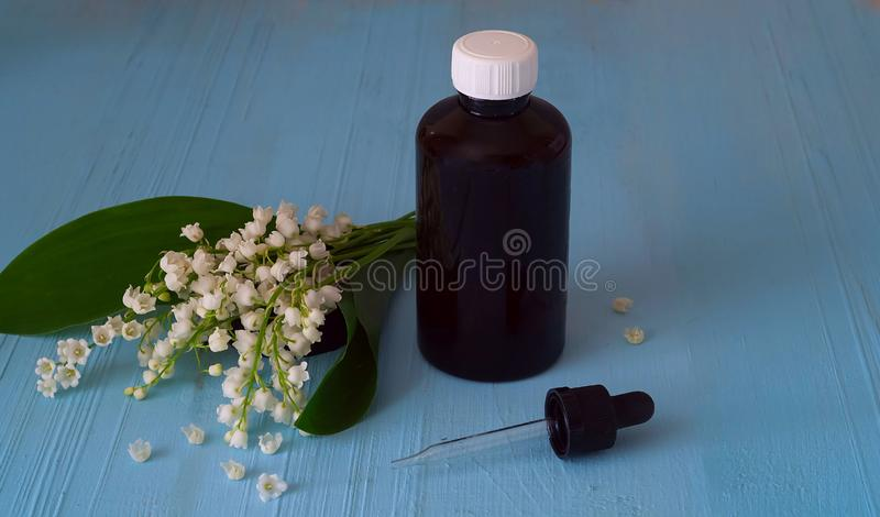 Lily of the valley, essential oilwith fresh Convallaria flowers on wooden background,concept of ecological ingredients, copy space royalty free stock photos