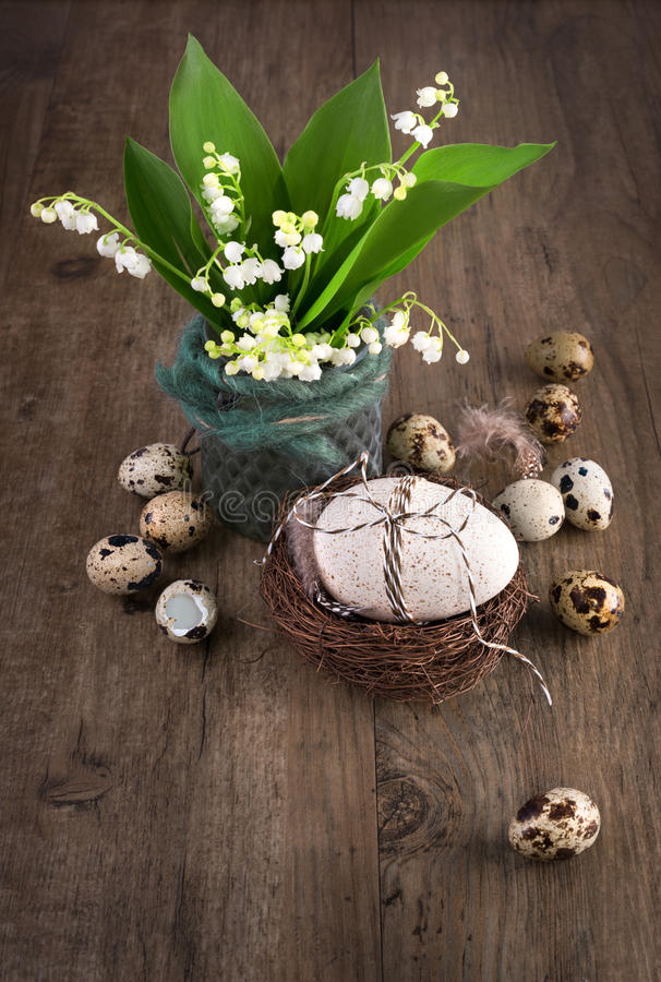 Lily of the valley and Easter decorations on old wood, text space stock photos