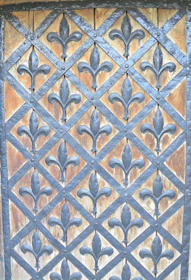 Lilys forjados en la puerta imagen de archivo