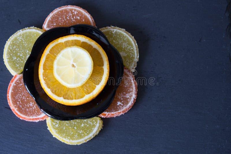 Limão colorido do doce de fruta e partes alaranjadas com açúcar e cortados imagem de stock