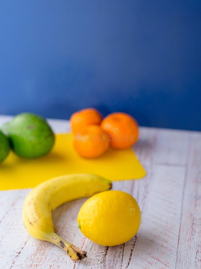Limão com banana em uma tabela de madeira com fundo azul imagem de stock royalty free