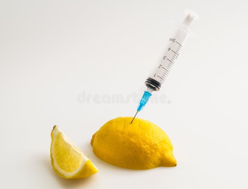Limão com seringa imagem de stock