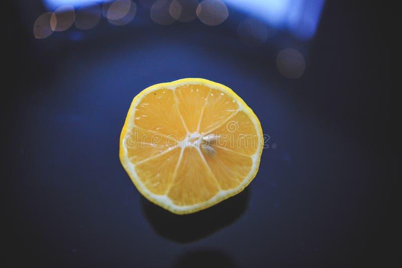 Limão de Meyer da cor alaranjada que origina em China tomada de um ângulo de 45 graus no fundo reflexivo preto fotos de stock royalty free