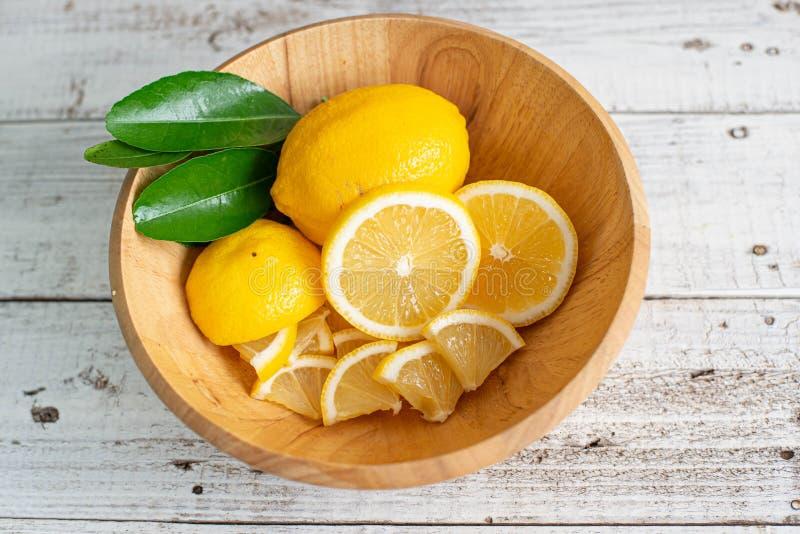 Limão e fatias orgânicos com a folha na bacia de madeira imagem de stock