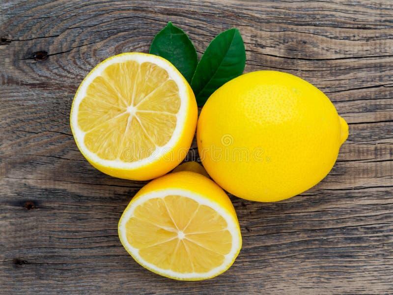 Limão fresco e metade eliminada na tabela velha de madeira, vista superior foto de stock royalty free