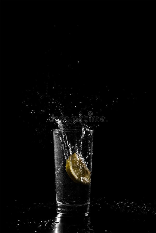 Limão que deixa cair em uma bebida fria fotografia de stock royalty free