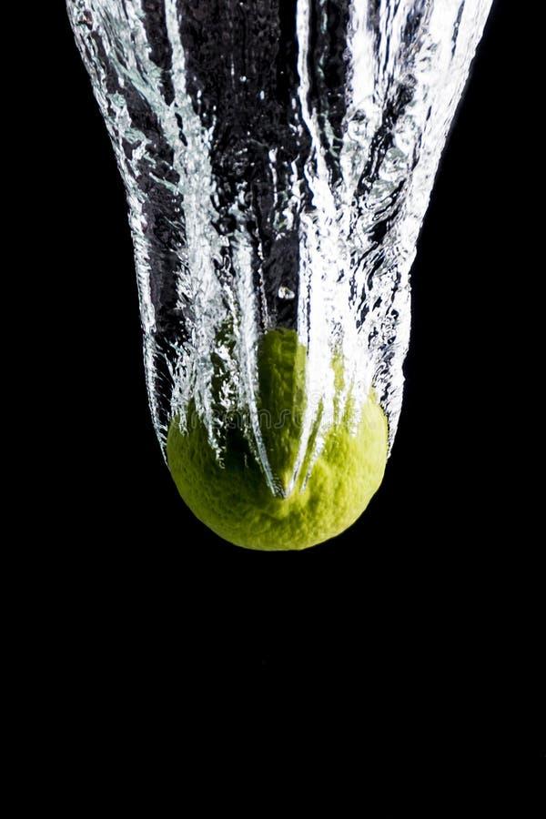 Limão que deixa cair na água que cria o respingo imagens de stock royalty free