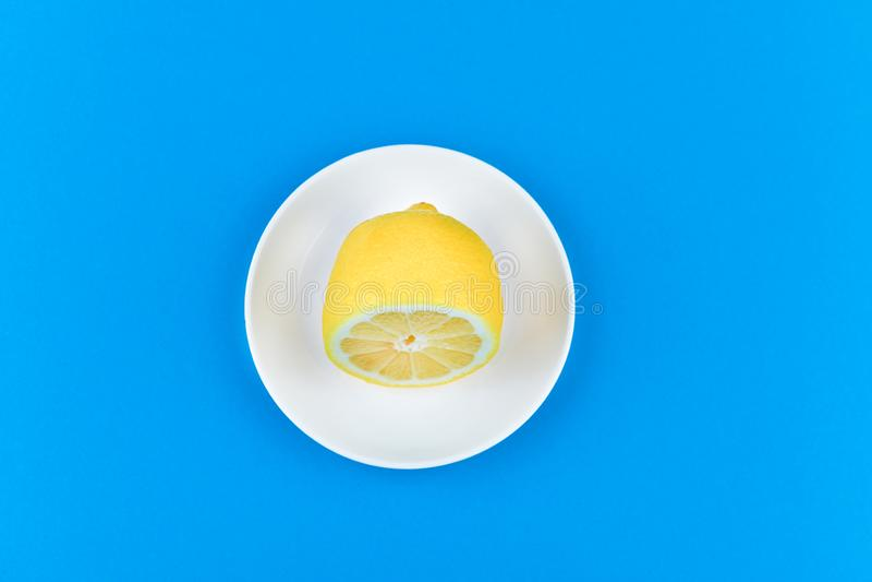 Limão sobre fundo azul repousa sobre uma placa branca limão de corte ver a partir de cima local para registrar Fatias de limão em foto de stock