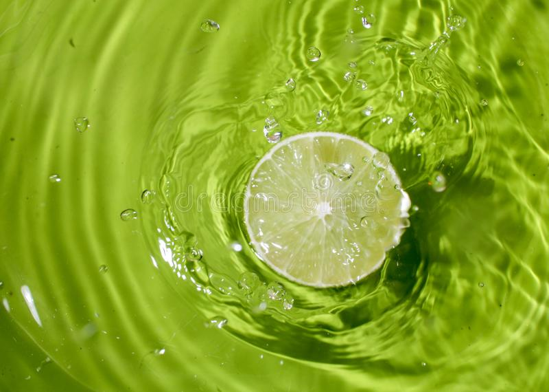 Limão verde no respingo da água imagem de stock