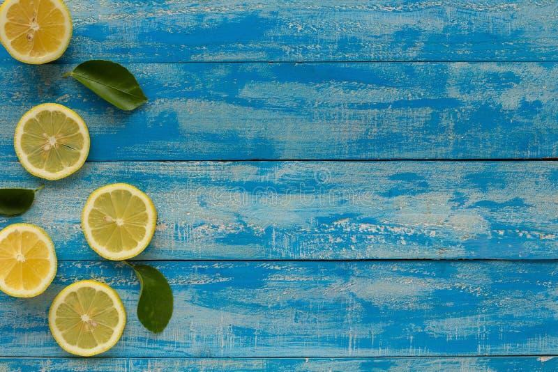 Limón amarillo en un fondo de madera azul Visión superior imagen de archivo