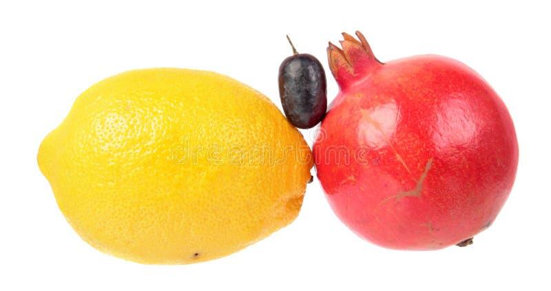 Limón amarillo, granada roja y baya púrpura de la uva aislados en el fondo blanco Ingredientes para la ensalada fotografía de archivo