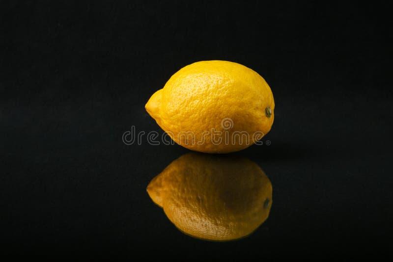 Limón entero en un fondo negro imagen de archivo