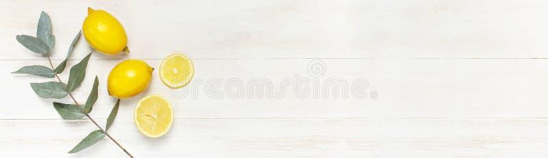 Limón fresco entero y cortado, hojas del eucalipto en el fondo de madera blanco Endecha plana, visión superior, espacio de la cop imagenes de archivo