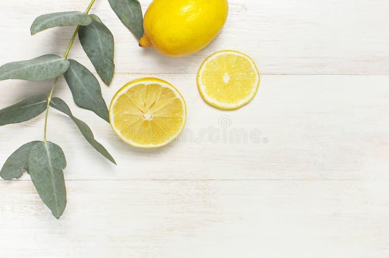 Limón fresco entero y cortado, hojas del eucalipto en el fondo de madera blanco Endecha plana, visión superior, espacio de la cop fotos de archivo libres de regalías