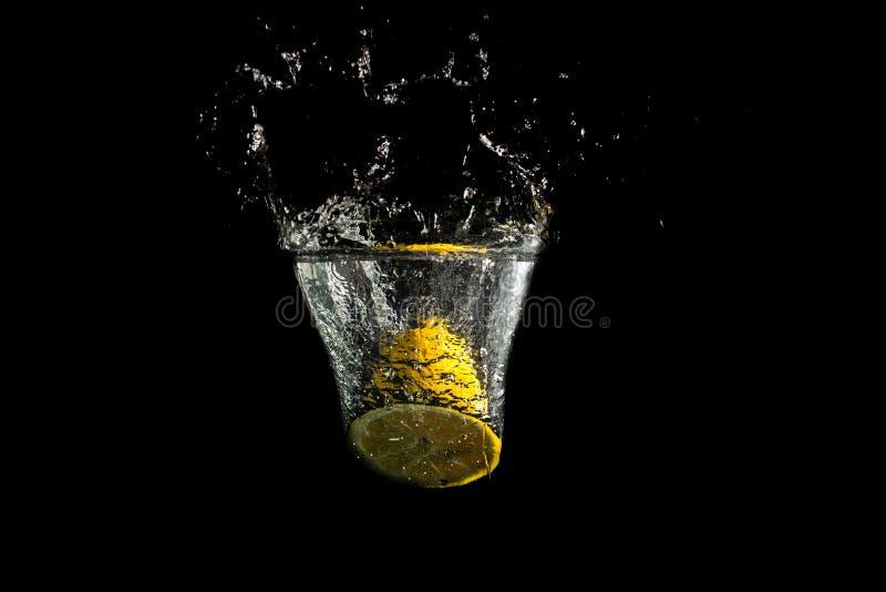 Limón fresco partido en dos que salpica en el agua potable fotografía de archivo
