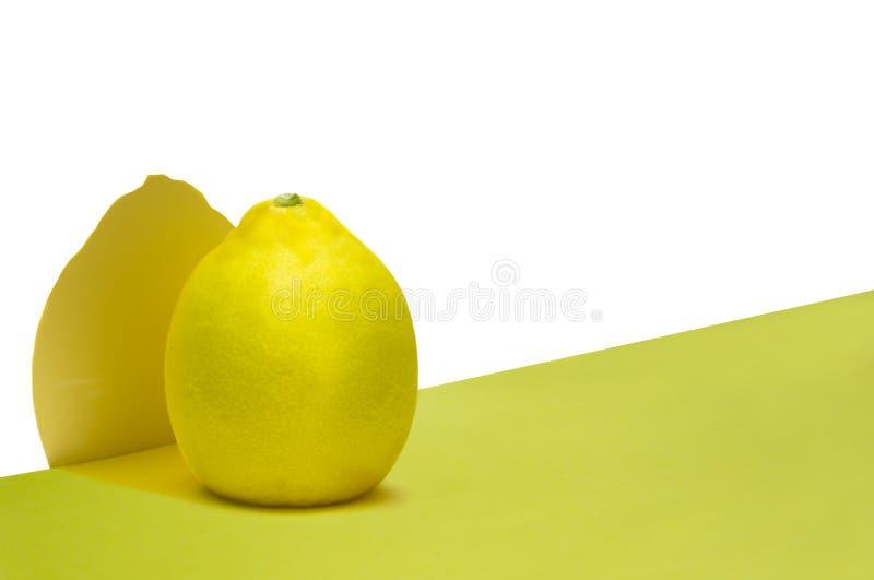 Limón sobre el fondo blanco y amarillo con la sombra imágenes de archivo libres de regalías