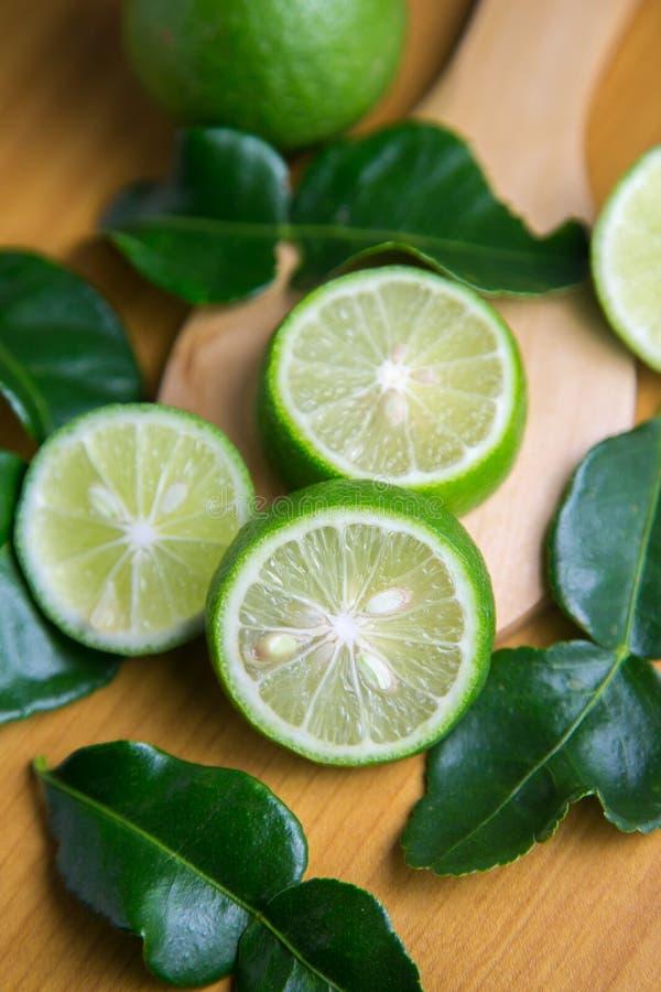 Limón verde fresco cortado en un fondo de madera marrón imagenes de archivo