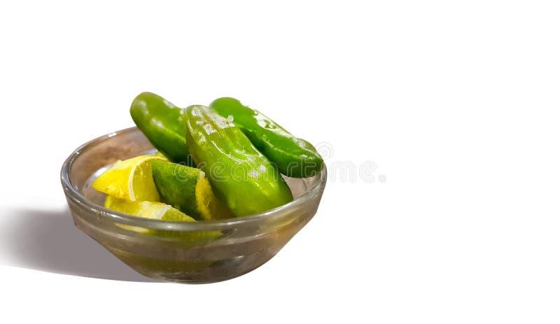 Limón y chiles verdes en un bol de vidrio en un fondo blanco aislado imagenes de archivo