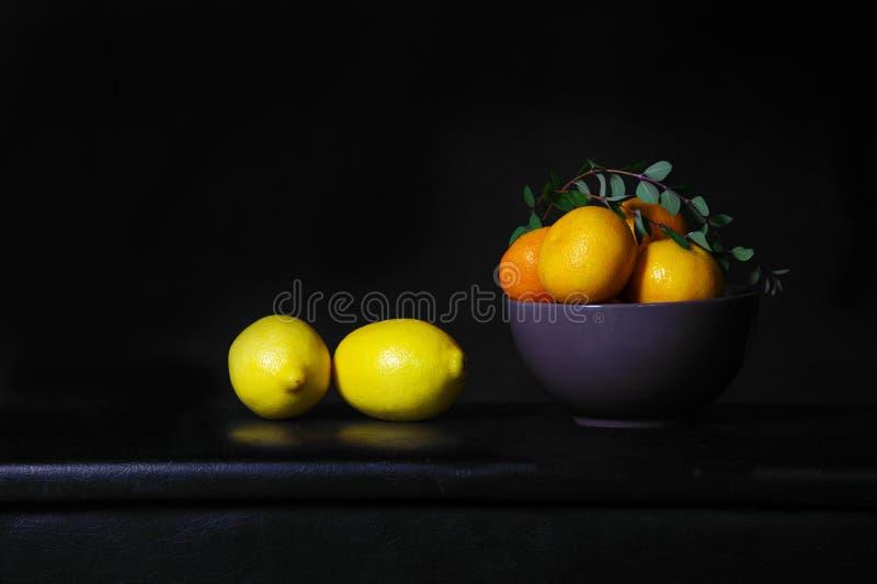 Limón y naranja amarillos en todavía la obra clásica de cerámica gris l del cuenco imagenes de archivo