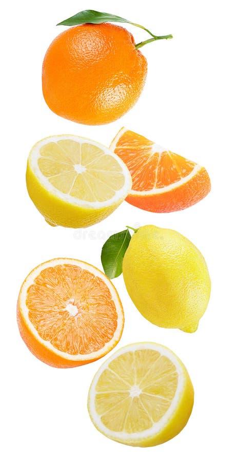 Limón y naranja que caen aislados en blanco imagenes de archivo