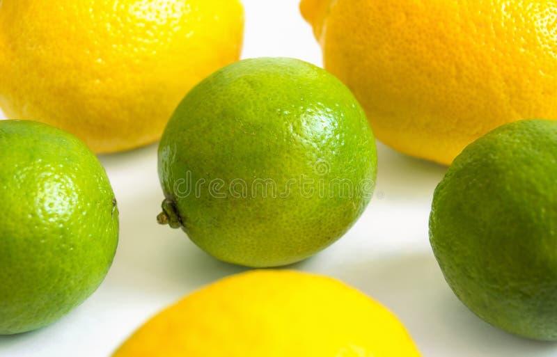Limões amarelos e cais verdes em um fundo branco fotografia de stock