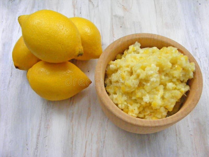 Limões amarelos em um fundo de madeira gasto branco com puré dos limões no potenciômetro de madeira imagens de stock