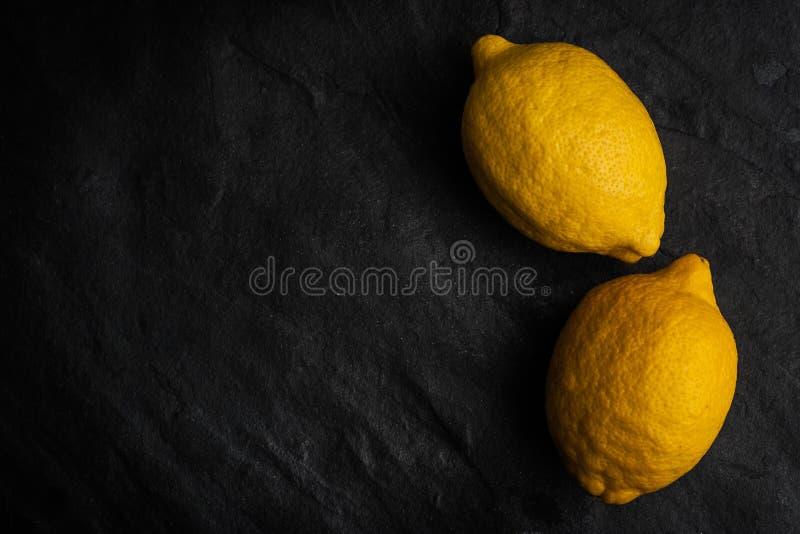 Limões amarelos no lado direito da tabela de pedra preta fotos de stock royalty free