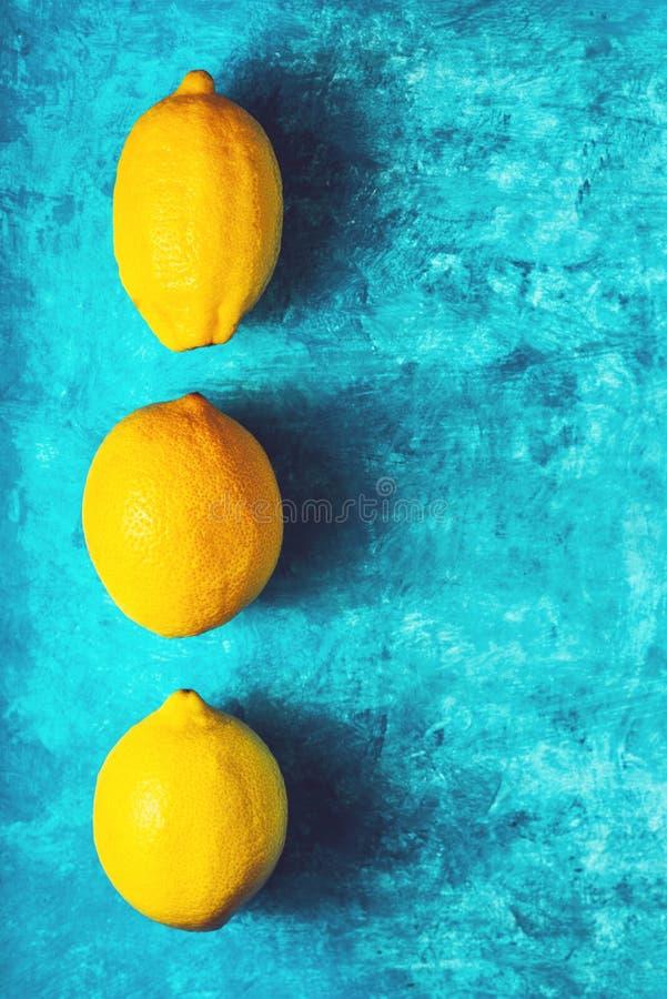Limões amarelos no vertical ciano do fundo fotografia de stock royalty free