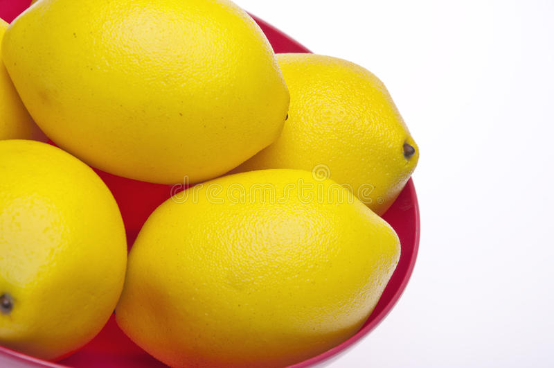 Limões amarelos vibrantes em uma bacia cor-de-rosa foto de stock