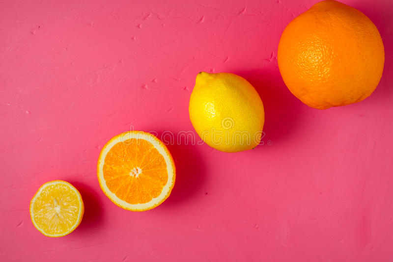 Limões e laranjas na opinião superior do fundo cor-de-rosa brilhante fotos de stock royalty free