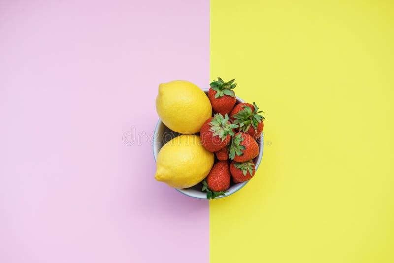 Limões e morangos frescos em uma bacia em um CCB amarelo e cor-de-rosa foto de stock