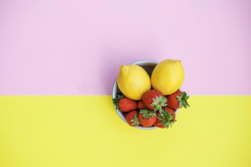 Limões e morangos frescos em uma bacia em um CCB amarelo e cor-de-rosa imagem de stock royalty free