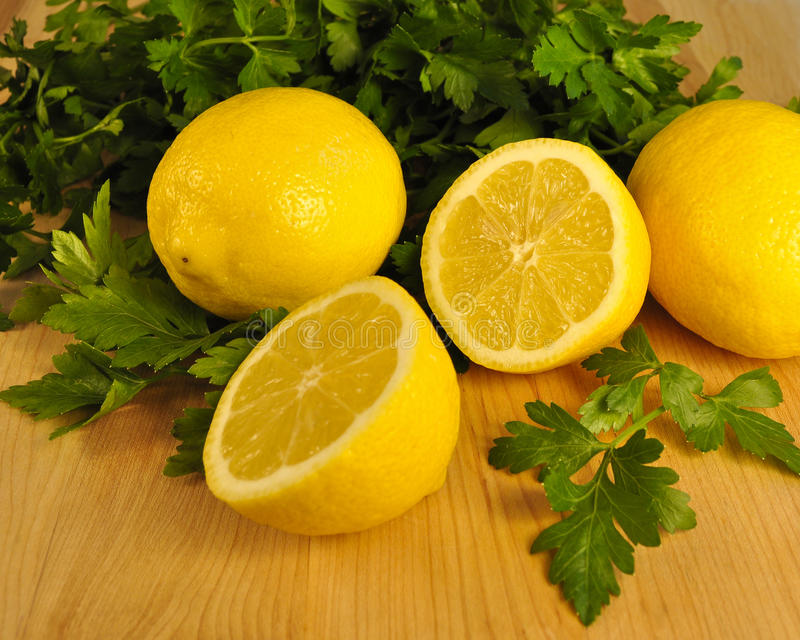 Limões frescos do corte e salsa lisa da folha imagens de stock royalty free