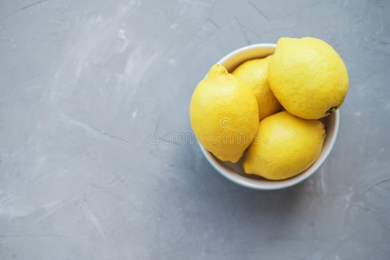 Limões frescos em uma bacia azul em um fundo cinzento imagens de stock royalty free