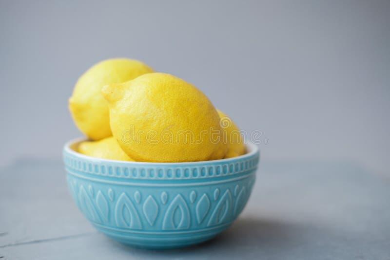 Limões frescos em uma bacia azul em um fundo cinzento imagem de stock