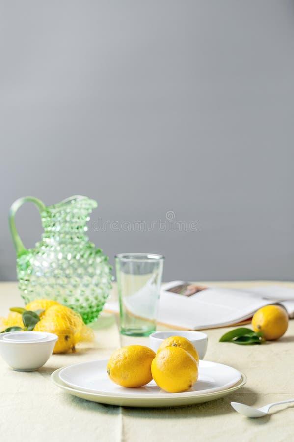 Limões maduros em uma placa, em um jarro, em um vidro e em um livro na tabela fotografia de stock
