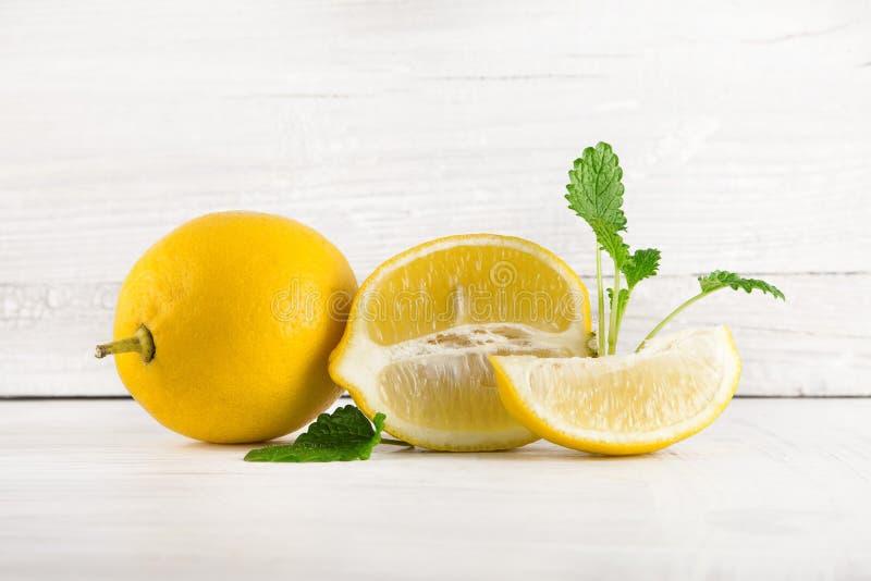 Limões maduros frescos, fatias, fotografia rústica do alimento na mesa de cozinha de madeira branca da placa imagem de stock royalty free