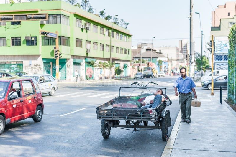 LIMA, PÉROU - 15 AVRIL 2013 : La personne dort dans la rue Un homme marche en la moto Temps de sièste photos stock