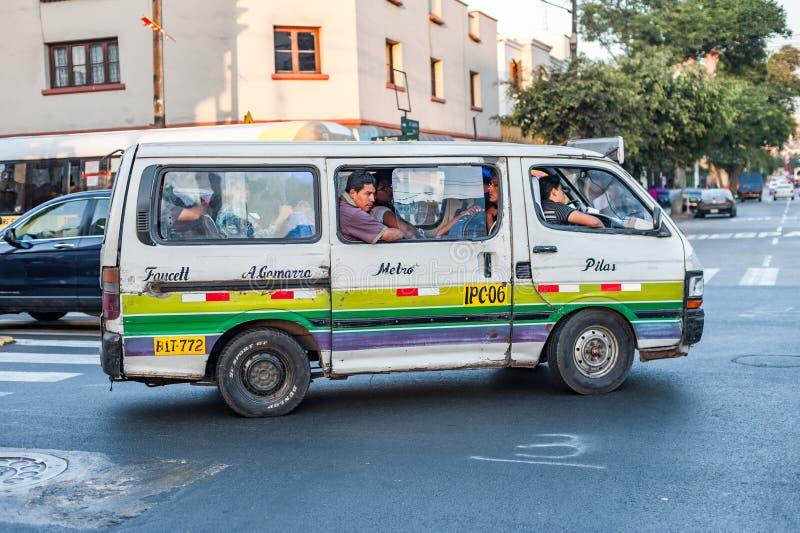 LIMA, PERÙ - 12 APRILE 2013: Vecchi bus dei furgoni in via di Lima ed estremamente pieno della gente Itinerario di Pilas - di Fau immagini stock libere da diritti