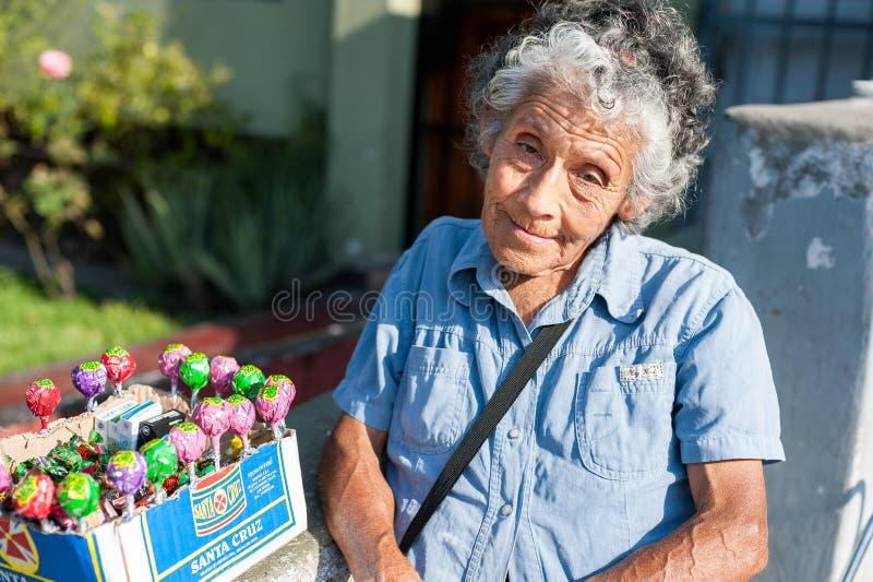 LIMA, PERU - APRIL 12, 2013: Een niet geïdentificeerde Peruviaanse vrouw die Chupa Chups-snoepjes op de straat verkopen Geïsoleer stock foto's
