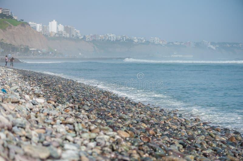 LIMA, PERU - 14 DE ABRIL DE 2013: Linha de oceano de South Pacific em Miraflores, Lima, Peru Duas pessoas no fundo imagem de stock