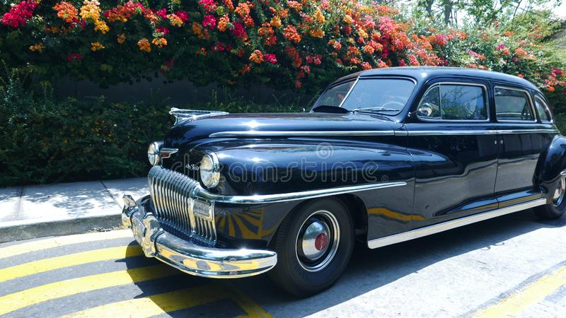 Black Desoto limousine parked in San Isidro, Lima. Lima, Peru. December 19, 2016. Front and side view of a mint condition black DeSoto limousine parked in a stock images