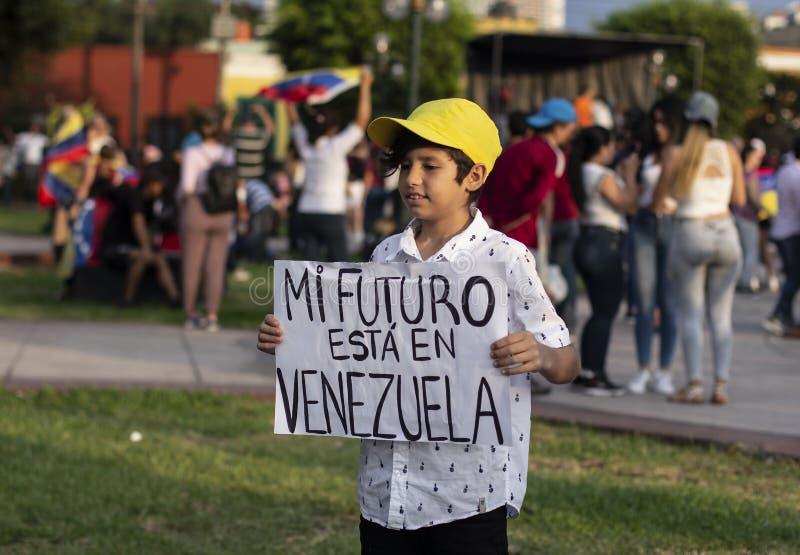 Cute little boy holding sign at protest. Lima, Peru - February 2 2019: Adorable cute boy holding sign displaying my future is in Venezuela mi futuro esta en royalty free stock image