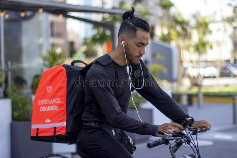 Good looking man in bike working for Rappi food delivery service. Lima, Peru - March 3 2019: Good looking man riding bike working for Rappi food delivery service stock image