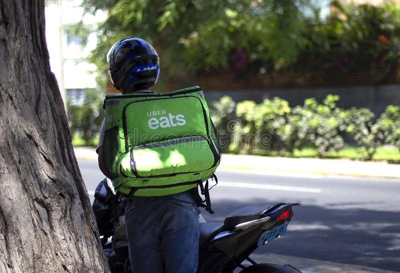 Uber eats driver working at food delivery service. Lima, Peru - March 3 2019: Uber eats driver working at food delivery service. Sharing collaborative economy royalty free stock photo