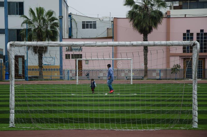 Lima Peru - OKTOBER 28th 2017: Fader och son som spelar med lodisar royaltyfri foto